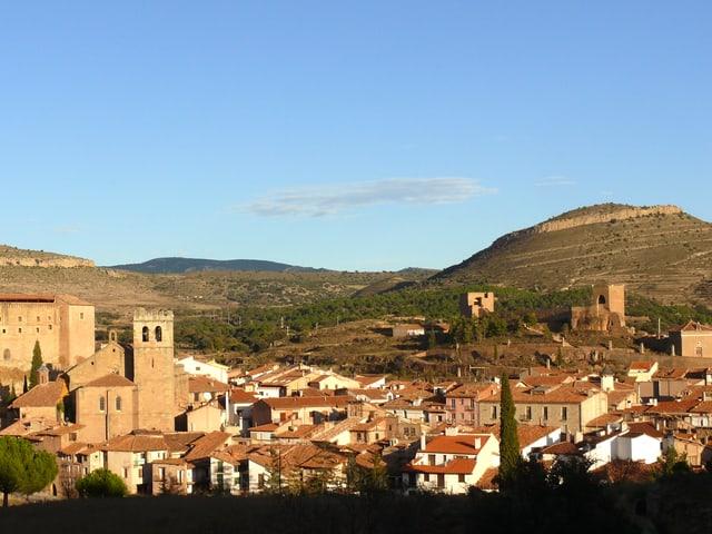 Eine Foto zeigt den spanischen Ort Mora de Rubielos: die Dächer leuchten rot, der Himmel ist blau.