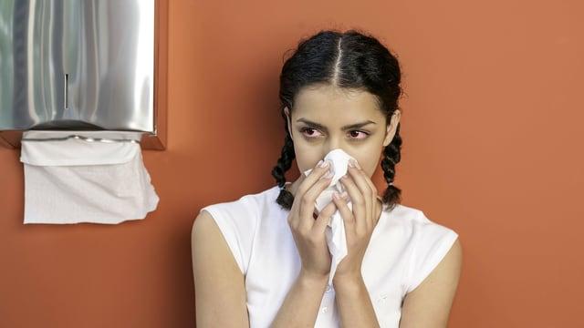 Junge Frau mit roten Augen schneuzt sich die Nase neben einem Papiertuchspender aus Metall