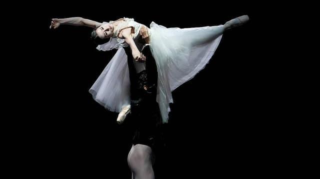 Ein Tänzer dreht eine Tänzerin in der Luft