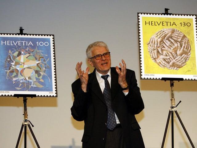 Ein Mann im Anzug stellt zwei Briefmarken vor.