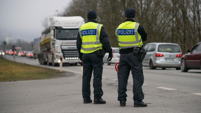 Zwei Polizisten von hinten fotographiert.