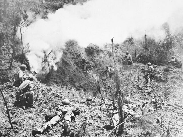 Soldaten beschiessen sich gegenseitig, im Hintergrund ist viel weisser Rauch zu sehen.