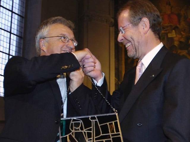 Beide tragen Blazer, Hemd und Krawatte. Zingg hat einen Dreitagebart. Beide tragen eine Brille. Sie schütteln sich die Hände, und Büttiker erhält ein Wappen, aus Metall und farbigem Glas.