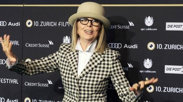 Frau mit kariertem Jacket und Hut und Hornbrille vor der Fotowand des Zurich Film Festivals.