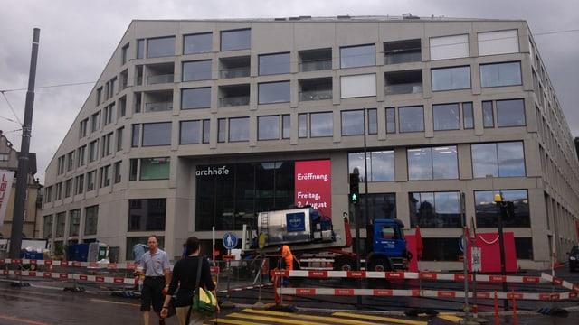 Aussenansicht des neuen Einkaufszentrums mit rotweissen Bauabschrankungen davor.