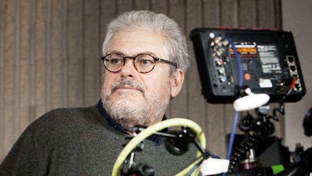 Roberto Andò mit Brille und schwarzen Pulli, neben einer Kamera.