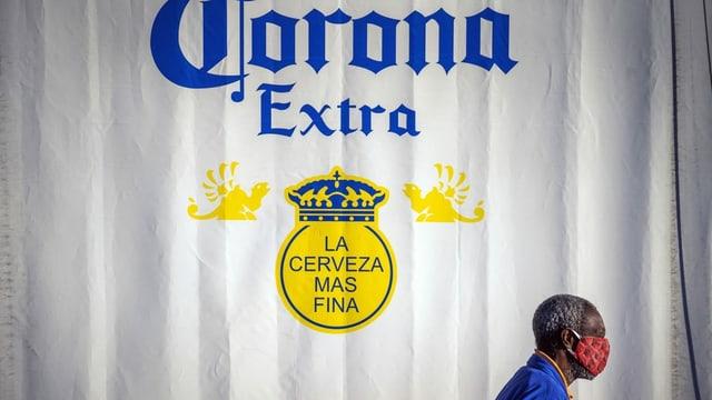 Ein Mann mit einer Maske vor einer Corona-Bierwerbung