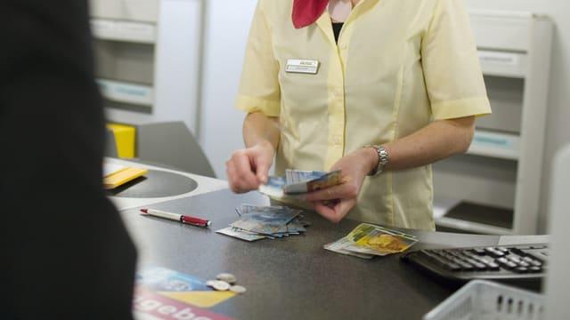 Eine Postangestellte bezahlt Bargeld aus.