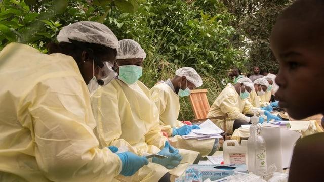 Pflegepersonal trägt Hygienemasken, Handschuhe und Umhänge, sie beugen sich über Listen mit Testergebnissen.