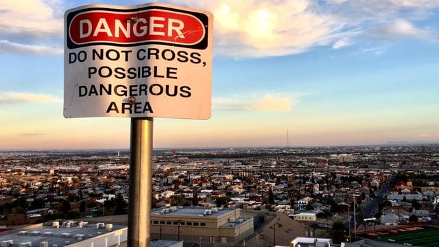 Ein Gefahrenschild vor einer Stadtkulisse.
