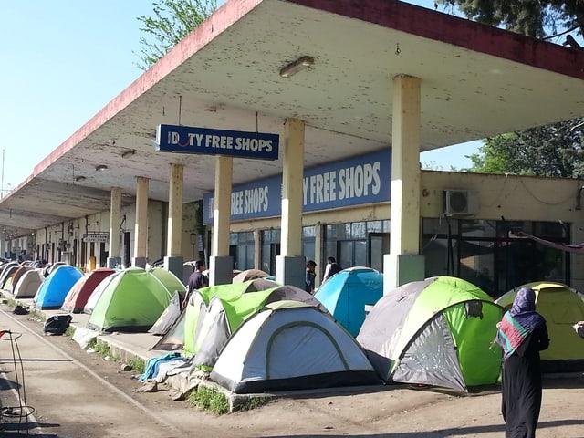 Zeltiglus stehen Reihe an Reihe unter einem heruntergekommenen Bahnhofssteg.