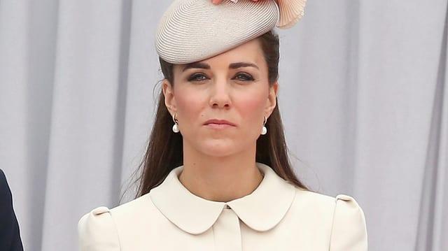 Kate mit Hut und ernstem Gesicht.