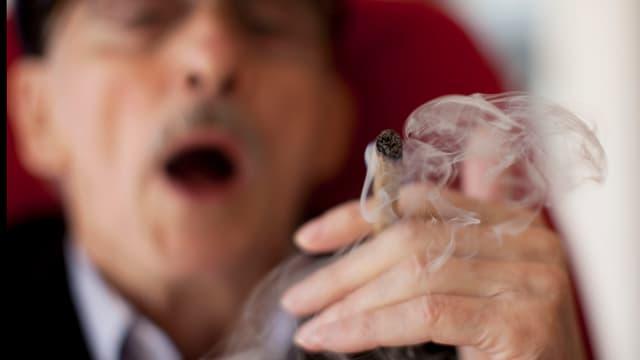 Ein älterer Mann raucht einen Joint.