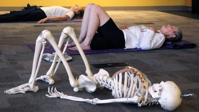 Zwei Leute liegen auf dem Boden. Neben ihnen liegt auch ein Skelett-Modell.