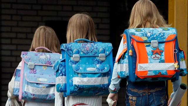 Drei Schulkinder auf dem Weg in die Schule.