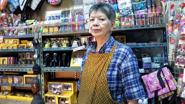 Eine Frau mit gelber Schürze steht im Laden.