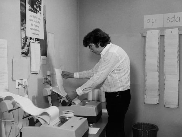 Mann vor einer Maschine mit einer langen Papierrolle.