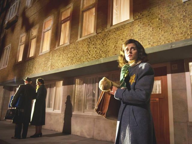 Anne Frank steht vor einem Gebäude. Sie trägt einen Judenstern.