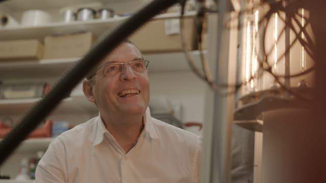 Auf dem Bild ist Hansjürg Leibundgut zu sehen wie er einen technischen Apparat betrachtet.