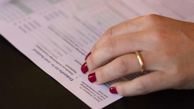 Eine Frau füllt eine Steuererklärung aus und trägt eineen Ehering.