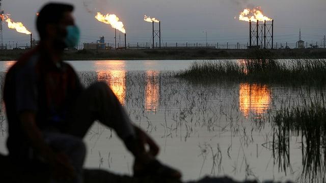 Mann mit Gesichtsmaske sitzt vor brennenden Schloten von Ölförderanlagen.