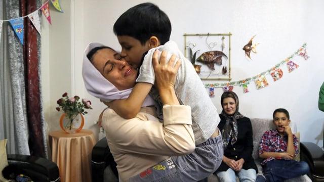 Eine Frau umarmt ihren Sohn.