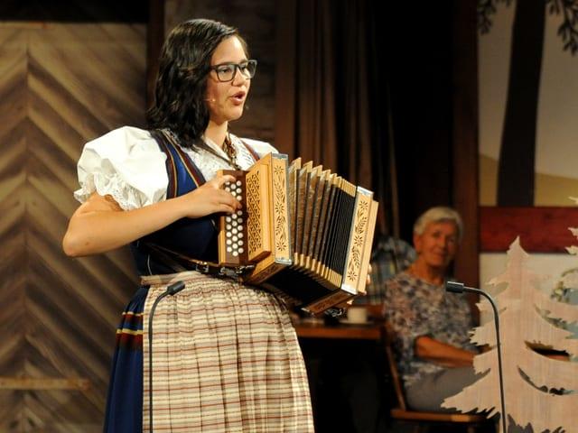 Madlene Husistein mit Schwyzerörgeli in der Hand singt und musiziert in schöner Tracht