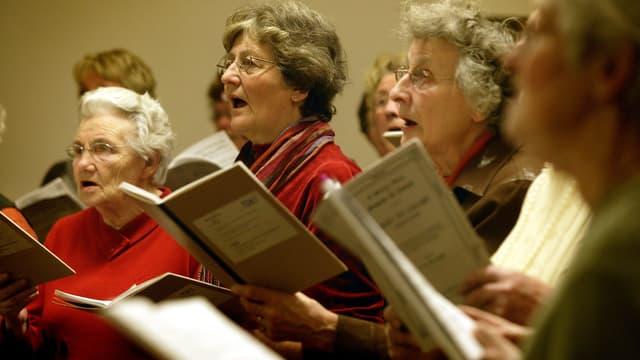 Ältere Frauen mit Gesangsbüchern.
