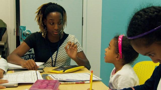Junge Frau am Tisch mit Schulbüchern und kleines Mädchen.