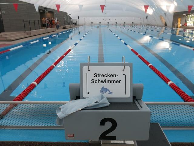 Das Bassin im Hallenbad mit der Bahn für schnelle Schwimmer. Auf dem Schild steht Streckenschwimmer und ein Delphin ist abebildet.