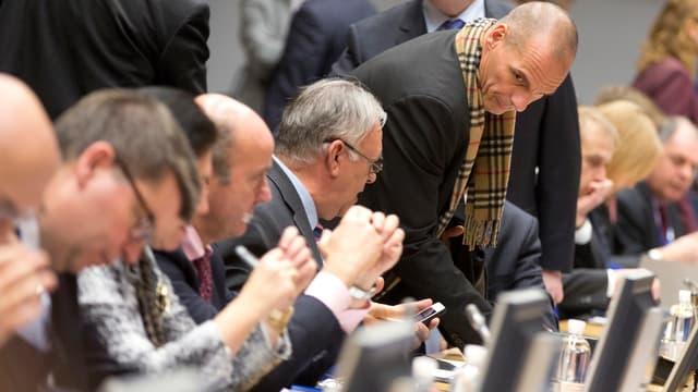 Griechenlands Finanzminister Gianis Varoufakis steht neben dem sitzenden Jean-Clude Juncker