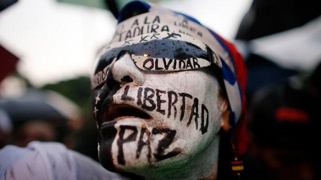 """Eine weibliche Demonstrantin hat sich die Wörter Freiheit, Frieden und """"wir vergessen nicht"""" auf das Gesicht gemalt."""