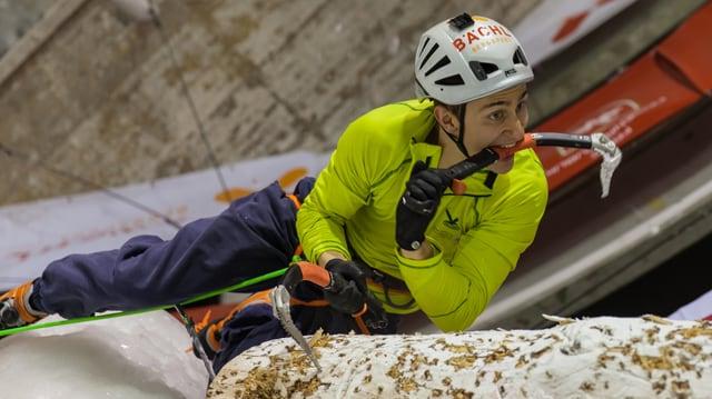 Kletterer mit Helm und Pickel im Mund