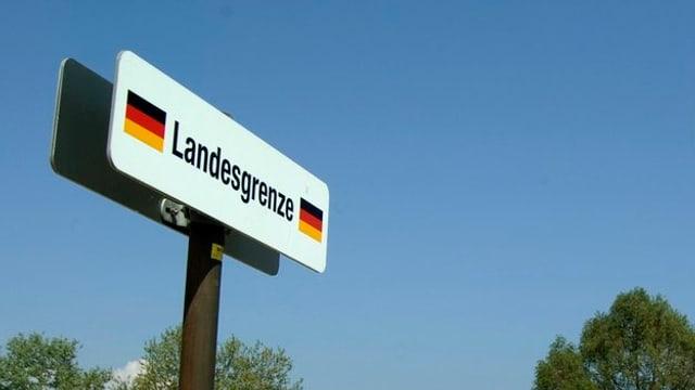 Il cunfin tranter la Svizra e la Germania a Constanza. Ins vesa ina tavla cun scrit si Landesgrenze e la bandiera da la Germania dad omaduas varts dal pled.