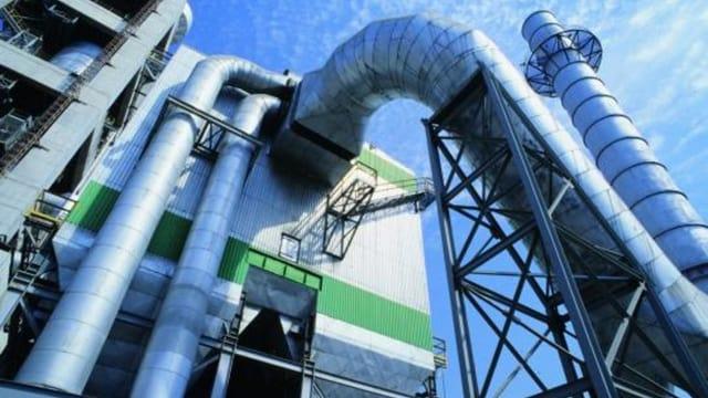 Blick von unten auf eine Zementfabrik mit Zuleitungsrohren für das Rohmaterial.