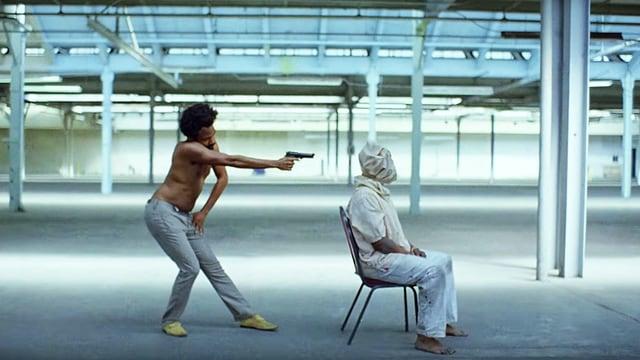 Ein Mann sitzt auf dem Stuhl, ein anderer schiesst ihm in den Kopf.