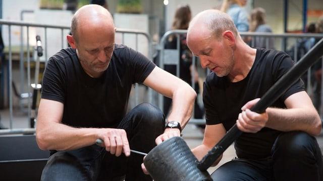 Zwei Männer werkeln an einer Installation herum.