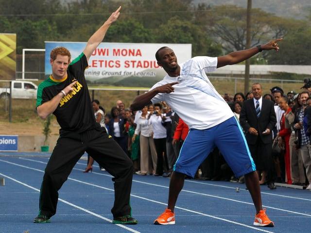 Prinz Harry posiert mit Olympia-Goldmedaillengewinner Usain Bolt.