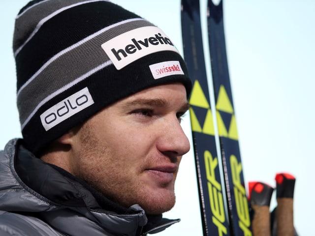 Dario Cologna posiert mit Skiern und Stücken.