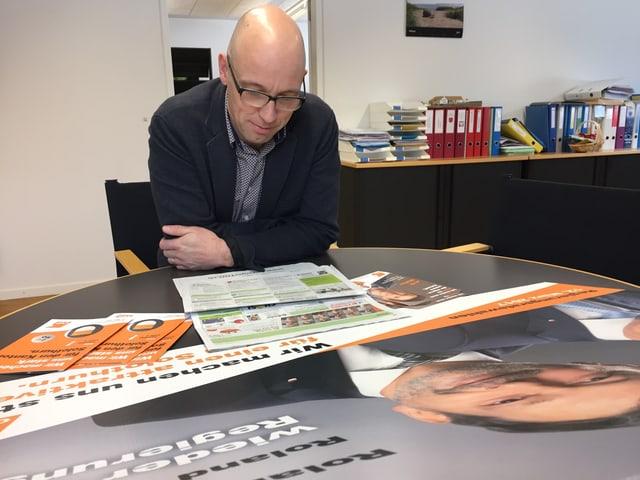 Mann sitzt an Bürotisch und studiert Plakate