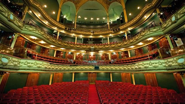 Farbaufnahme der Oper in Antwerpen innen mit roten Stühlen und grüner Decke