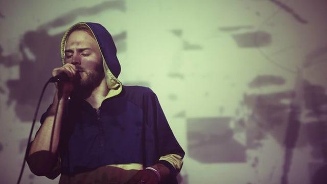 ein mann mit kapuze singt mit geschlossenen augen