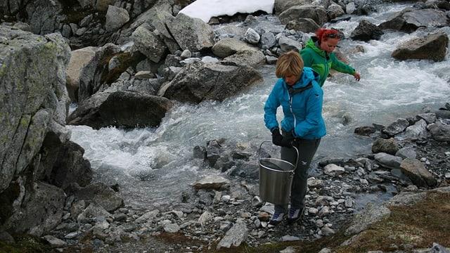 Sabine Dahinden holt Wasser im Bergbach.