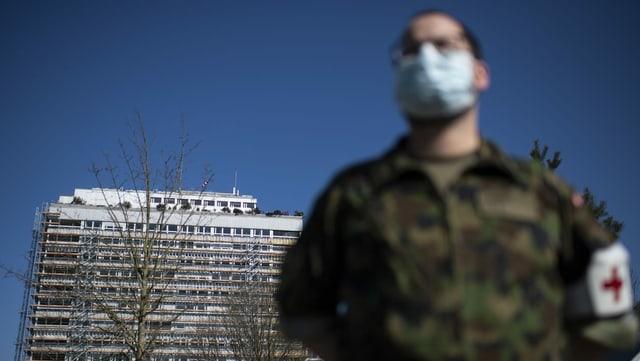 Ein Soldat mit Gesichtsmaske vor dem Bettenhochhaus.