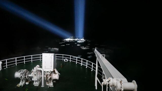 Auf Eis im Meer leuchten die Strahler eines Schiffes.