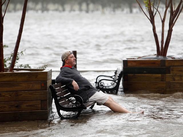 Mann sitzt auf Bank, Strasse überflutet.