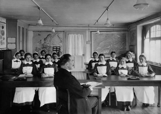 Junge Frauen in Diakonissenkleidung sitzen an Pulten, ein Mann sitzt mit Dokumenten vor ihnen
