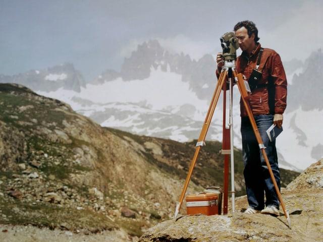 Mann in den Bergen, schaut durch Messgerät.