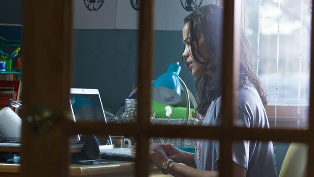 Hinter einer Glastüre sitzt eine junge Frau an einem Tisch vor ihrem Laptop.