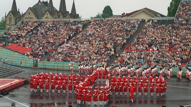 Viele Leute auf Tribüne schauen Aufführung.